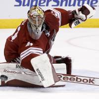 Photo - Phoenix Coyotes' Mike Smith looks at the puck after it hit the post during the first period of an NHL hockey game against the Florida Panthers, Thursday, March 20, 2014, in Glendale, Ariz. (AP Photo/Ross D. Franklin)