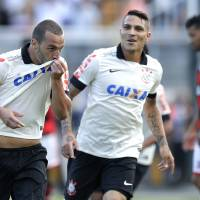 Photo - Corinthians' Guilherme, left, celebrates with teammate Paolo Gerrero after scoring against Flamengo during a Brazilian soccer league match in Sao Paulo, Brazil, Sunday, April 27, 2014. (AP Photo/Andre Penner)