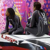 Photo - The team from the United States USA-1, piloted by Elana Meyers with brakeman Lauryn Williams, left, wait for scores after their first run during the women's two-man bobsled competition at the 2014 Winter Olympics, Tuesday, Feb. 18, 2014, in Krasnaya Polyana, Russia. (AP Photo/Dita Alangkara)