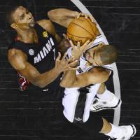 Photo - Miami Heat's Chris Bosh and San Antonio Spurs' Tim Duncan go after a rebound during the second half of Game 4 of the NBA Finals basketball series, Thursday, June 13, 2013, in San Antonio. (AP Photo/Larry W. Smith, Pool)