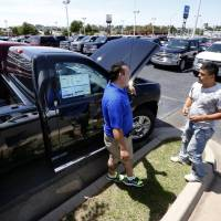 Photo - Sales representative Tino Medina, left, talks with car shopper Ricardo Cruz at David Stanley Chevrolet on Interstate 240 and Walker Avenue.  Dealerships have started to see customers with insurance checks to spend on a new vehicle following May tornadoes.  STEVE SISNEY - THE OKLAHOMAN
