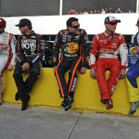 Photo - Dale Earnhardt Jr, Martin Truex Jr., Tony Stewart, Kevin Harvick and Dave Blaney, from left, chat as they sit on pit wall before qualifying for Sunday's NASCAR Sprint Cup series auto race at Charlotte Motor Speedway in Concord, N.C., Thursday, May 22, 2014. (AP Photo/Mike McCarn)