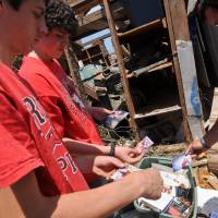 Photo - Brian Roberts,14, (left) and Caden Powell, 13, (middle) show Michael Roberts (right) photos that they pulled from a tub in a ruined storage shed in their back yard. Photo by KT King, The Oklahoman