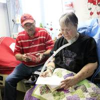 Photo - Ed Hutchison opens a Christmas present for his wife, Glenda Kay, in her room at Kindred Hospital in Oklahoma City. Photo by SARAH PHIPPS, the Oklahoman