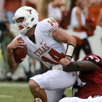 Photo -   Texas quarterback David Ash (14) is sacked by Oklahoma defensive tackle Casey Walker (53) during the second half of an NCAA college football game at the Cotton Bowl Saturday, Oct. 13, 2012, in Dallas. Ash left the game injured after the play and did not return to the game. Oklahoma won 63-21. (AP Photo/Michael Mulvey)