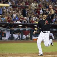 Photo - As teammate Miguel Montero's bat goes flying into the air, Arizona Diamondbacks' Ender Inciarte raises his arm in celebration as he comes in to score a run on a 3-run double by Montero against the Chicago Cubs during the fifth inning of a baseball game on Saturday, July 19, 2014, in Phoenix. (AP Photo/Ross D. Franklin)