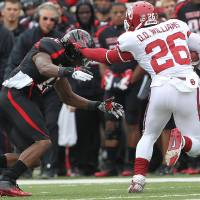 Photo -   Oklahoma's Damien Williams tries to get past Texas Tech's D.J. Johnson during an NCAA college football game in Lubbock, Texas, Saturday, Oct. 6, 2012. (AP Photo/Lubbock Avalanche-Journal, Stephen Spillman) LOCAL TV OUT