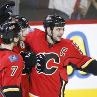 Photo - Calgary Flames' Matt Stajan, center, celebrates his goal with teammates TJ Brodie, left, and Mark Giordano during second period NHL hockey action in Calgary, Canada, Wednesday, Jan. 22, 2014. (AP Photo/The Canadian Press, Jeff McIntosh)