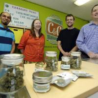 Photo - In this June 23, 2014 photo, Pete O'Neil, right, stands in his soon-to-be-open medical marijuana dispensary in Seattle with three of his employees. O'Neil struck out in Washington's lottery for coveted pot-shop licenses, and he has unsuccessfully tried to buy companies who did. In frustration, he's turning what would have been his Seattle retail store into a medical marijuana dispensary. Also pictured are Patricia Barker, second from left, grower representative, Adam Girton, second from right, product line advisor, and John Minehart managing director of U.S. Cannabis. (AP Photo/Ted S. Warren)