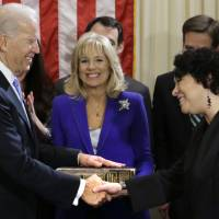 Photo - Vice President Joe Biden, with his wife Jill Biden, center, holding the Biden Family Bible, shakes hands with Supreme Court Justice Sonia Sotomayor after taking the oath of office during an official ceremony at the Naval Observatory, Sunday, Jan. 20, 2013, in Washington. (AP Photo/Carolyn Kaster)