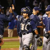 Photo - San Diego Padres catcher Rene Rivera, center, celebrates with teammates after the Padres' 13-3 win over the Chicago Cubs in a baseball game Thursday, July 24, 2014, in Chicago. (AP Photo/Charles Rex Arbogast)