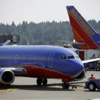 Photo - In this June 11 photo, a tug pushes a Southwest Airlines airliner away from a gate at SeaTac Airport in SeaTac, Wash. Southwest Airlines Co. broke a string of three straight losing quarters July 21  by scratching out a small profit in the April-June period despite a downturn in travel. (AP Photo/David Zalubowski)