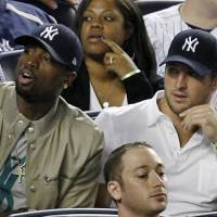Photo -   Miami Heat's Dwayne Wade, left, sits beside New York Jets quarterback Tim Tebow during the New York Yankees baseball game against the Los Angeles Angels at Yankee Stadium in New York, Sunday, April 15, 2012. (AP Photo/Kathy Willens)