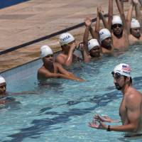 Photo -   U.S. Olympic swimming champion Michael Phelps speaks to young swimmers in the pool at the Olympic Village Carlos Castilho where they regularly train in the Complexo de Alemao slum as he leads a workshop sponsored by Visa in Rio de Janeiro, Brazil, Tuesday, Oct. 30, 2012. (AP Photo/Silvia Izquierdo)