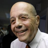 Photo - FILE - In this Wednesday, June 25, 2014 file photo, former Providence Mayor Buddy Cianci speaks with reporters at the WPRO-AM radio station in East Providence, R.I., after announcing on the air that he will run for a seventh term as mayor. Cianci was forced to resign in 1984 after he was convicted of assault. In 1990 he won his job back until he was convicted of racketeering conspiracy in 2002 and sent to prison as part of a federal investigation into corruption in City Hall. (AP Photo/Steven Senne, File)