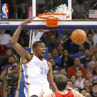Photo - Oklahoma City Thunder forward Kevin Durant (35) dunks in front of Houston Rockets forward Omri Casspi (18) during the first quarter of an NBA basketball game, Sunday, Dec. 29, 2013, in Oklahoma City. (AP Photo/Alonzo Adams)