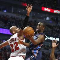 Photo - Charlotte Bobcats guard Kemba Walker (15) shoots past Chicago Bulls forward Taj Gibson (22) during the first half of an NBA basketball game Monday, Dec. 31, 2012, in Chicago. (AP Photo/Charles Rex Arbogast)