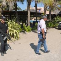 Photo - Police patrol on the beach outside a home after masked armed men broke into the home in Acapulco, Mexico, Tuesday Feb. 5, 2013. According to the mayor of Acapulco, five masked men burst into the house that Spanish tourists had rented on the outskirts of Acapulco, in a low-key area near the beach, and held a group of six Spanish men and one Mexican woman at gunpoint, while they raped the six Spanish women before dawn on Monday. (AP Photo/Bernandino Hernandez)