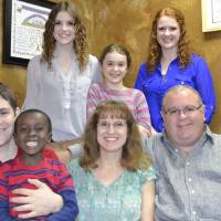 Photo - The Cloud family, standing left to right, front row: Ben, Kangwa, Marcia and Randy Cloud.  Second row, Katie, Melanie and Lauren Cloud.  Kangwa came to the United States in June as part of a combined foster parenting adoption program.  Provided photo