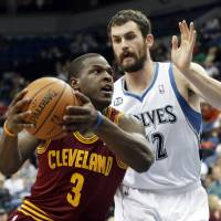Photo - Cleveland Cavaliers' Dion Waiters, left, drives around Minnesota Timberwolves' Kevin Love in the second half of an NBA basketball game Wednesday, Nov. 13, 2013, in Minneapolis. The Timberwolves won 124-95. (AP Photo/Jim Mone)