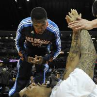 Photo - Oklahoma City Thunder guard Nate Robinson talks with Denver Nuggets  forward Wilson Chandler during warm ups before the start of game 3 of a first-round NBA basketball playoff series Saturday, April 23, 2011, in Denver. (AP Photo/Jack Dempsey)