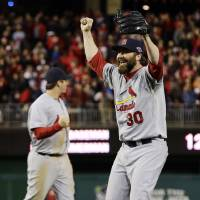 Photo -   St. Louis Cardinals relief pitcher Jason Motte, front, and third baseman David Freese react after Game 5 of the National League division baseball series against the Washington Nationals on Saturday, Oct 13, 2012, in Washington. St. Louis won 9-7. (AP Photo/Alex Brandon)
