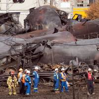 Photo -   Workers stand before mangled tanker cars at the crash site of the train derailment and fire July 6 in Lac-Megantic, Quebec, Canada.  AP File Photos   Ryan Remiorz -  AP