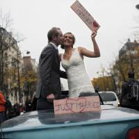 Photo -   A bride and a groom stand in a car as they protest against French President Francois Hollande's plan to legalize marriage and adoption for gay people, in Paris, Saturday Nov. 17, 2012. Saturday's event, entitled