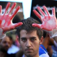 Photo - A Lebanese pro-Syrian regime supporter, his hands painted in red to symbolize blood, attends a demonstration against a possible military strike in Syria, near the U.S. Embassy in Aukar, east of Beirut, Lebanon, Friday, Sept. 6, 2013. The prospect of a U.S.-led strike against Syria has raised concerns of potential retaliation from the Assad regime or its allies. The State Department ordered nonessential U.S. diplomats to leave Lebanon over security concerns and urged private American citizens to depart as well. (AP Photo/Hussein Malla)