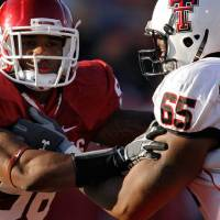 Photo - Oklahoma's Ronnell Lewis (56) takes on Texas Tech's LaAdrian Waddle (65) during the first half of the college football game between the University of Oklahoma Sooners (OU) and the Texas Tech Red Raiders (TTU) at the Gaylord Family-Oklahoma Memorial Stadium on Saturday, Nov. 13, 2010, in Norman, Okla.  Photo by Chris Landsberger, The Oklahoman