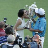 Photo - Jason Dufner, right, kisses the Wanamaker Trophy with his wife Amanda  after winning the PGA Championship golf tournament at Oak Hill Country Club, Sunday, Aug. 11, 2013, in Pittsford, N.Y. (AP Photo/Charlie Riedel)