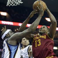 Photo - Cleveland Cavaliers' Tristan Thompson (13) gets an offensive rebound over Memphis Grizzlies' Zach Randolph, left, and Tayshaun Prince, center, during the first half of an NBA basketball game in Memphis, Tenn., Saturday, March 1, 2014. (AP Photo/Danny Johnston)