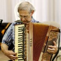 Photo -  George Secor plays at the monthly meeting of the Oklahoma City Accordion Club. Photo by Doug Hoke, The Oklahoman   DOUG HOKE
