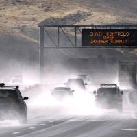 Photo - Traffic moves west along Interstate 80 west of Reno, Nev., as a heavy, wet storm hits Northern Nevada on Sunday, Dec. 2, 2012. A powerful storm delivered more snow and less rainfall Sunday to the Sierra than forecast, blunting the flooding danger on the Truckee River in California and Nevada, forecasters said. (AP Photo/Cathleen Allison)