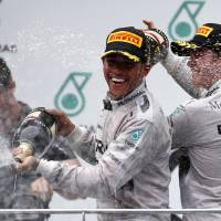 Photo - Mercedes driver Lewis Hamilton of Britain sprays champagne on the podium with teammate Nico Rosberg, right, after winning the the Malaysian Formula One Grand Prix at Sepang International Circuit in Sepang, Malaysia, Sunday, March 30, 2014. Rosberg finished in second place. (AP Photo/Vincent Thian)