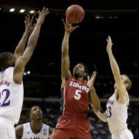 Photo - Stanford's Chasson Randle (5) gets between Kansas's Andrew Wiggins, left, Conner Frankamp (23) and k23=, right, to shoot during the first half of a third-round game at the NCAA college basketball tournament Sunday, March 23, 2014, in St. Louis. (AP Photo/Charlie Riedel)