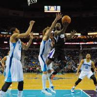 Photo - Sacramento Kings guard Tyreke Evans (23) shoots as New Orleans Hornets center Robin Lopez, center left, defends  as Hornets Anthony Davis, left, looks on in the first half of an NBA basketball game in New Orleans, Monday Jan. 21, 2013.  (AP Photo / Stacy Revere)