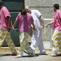 Photo - PRISON FASHION: Cleveland County inmates wear outlandish jail uniforms as they walk to the jail from court on Thursday , May 20, 2010, in Norman, Okla.  Photo by Steve Sisney, The Oklahoman ORG XMIT: KOD