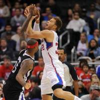 Photo - Los Angeles Clippers forward Blake Griffin, right, puts up a shot as Sacramento Kings center DeMarcus Cousins defends in the first half of an NBA basketball game in Los Angeles on Saturday, Dec. 1, 2012. (AP Photo/Richard Hartog)