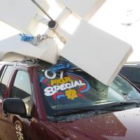 Photo - High winds toppled light poles onto vehicles at the Edmond Hyundai on the Broadway Extension in Edmond Monday afternoon. No one was hurt.  BY MATT DINGER