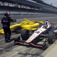 Photo - Will Power, (12) of Australia, waits as teammate Helio Castroneves, of Brazil, pulls out around him as they leave the pit area during practice for the Indianapolis 500 IndyCar auto race at the Indianapolis Motor Speedway in Indianapolis, Monday, May 19, 2014. (AP Photo/Michael Conroy