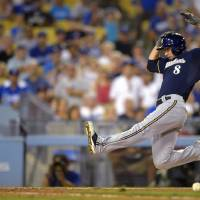 Photo - Milwaukee Brewers' Ryan Braun, right, scores on a single by Scooter Gennett as Los Angeles Dodgers catcher A.J. Ellis takes a late throw during the eighth inning of a baseball game, Friday, Aug. 15, 2014, in Los Angeles. (AP Photo/Mark J. Terrill)