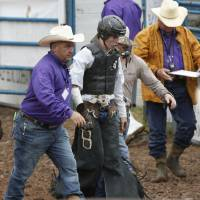 Photo -  Taylor Howell, of Warner, is guided from the arena floor after competing in the bareback bronc event Thursday at the IFR in Shawnee. Photo by Paul Hellstern, The Oklahoman   PAUL HELLSTERN -