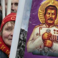 Photo - FILE - In this Saturday, Feb. 23, 2013 file photo a woman holds a portrait of Soviet dictator Josef Stalin during a communist rally marking the Defenders of the Fatherland Day in Moscow, Russia. An opinion survey commissioned by the Carnegie Endowment has revealed that Soviet dictator Josef Stalin has remained widely admired in Russia and other ex-Soviet nations despite his repressions that killed millions of people. It has found that support for Stalin in Russia has actually increased since the 1991 collapse of the Soviet Union. (AP Photo/Mikhail Metzel)