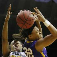 Photo - West Virginia center Asya Bussie (20) rejects a layup attempt by LSU guard Danielle Ballard (32) in the second half of an NCAA college basketball second-round tournament game Tuesday, March 25, 2014, in Baton Rouge, La. LSU won 76-67. (AP Photo/Rogelio V. Solis)