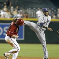 Photo - Milwaukee Brewers' Jean Segura, right, accidentally kicks Arizona Diamondbacks' Miguel Montero in the head while trying to leap over Montero on an inning ending double play during the sixth inning of a baseball game on Wednesday, June 18, 2014, in Phoenix. (AP Photo/Ralph Freso)
