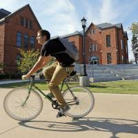 Photo - A cyclist rides past the east side of Old North on the campus of the University of Central Oklahoma, in Edmond, Okla., Monday, Aug. 20, 2012. Photo by Nate Billings, The Oklahoman