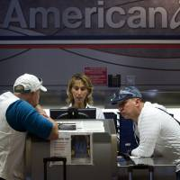 Photo -   FILE- In this Friday, Oct. 5, 2012, file photo, two unidentified American Airlines passengers talk to a customer service representative, center in Miami. Just weeks ago, American Airlines was working its way through bankruptcy court, on schedule for one of the fastest turnarounds in aviation history, but then, domestic traffic fell by 7.1 percent in September from the same month a year earlier. No other major airline experienced a drop like that. (AP Photo/J Pat Carter, File)