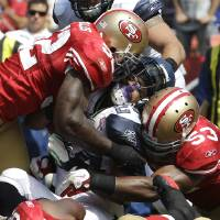 Photo -   FILE - In this Sept. 11, 2011 file photo, San Francisco 49ers linebackers Patrick Willis (52),backer NaVorro Bowman (53), and defensive tackle Ray McDonald (91) tackling Seattle Seahawks running back Marshawn Lynch (24) during the first quarter of an NFL football game in San Francisco. They are not only the biggest reason behind the 49ers' defensive success, they are a close bunch that has quickly become the new NFL standard for linebackers. Meet Patrick Willis, NaVorro Bowman, Aldon Smith and Ahmad Brooks. (AP Photo/Paul Sakuma, File)