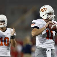 Photo - Oklahoma State's Wes Lunt (11) and Clint Chelf (10) warm up before the college football game between the University  of Arizona and Oklahoma State University at Arizona Stadium in Tucson, Ariz.,  Saturday, Sept. 8, 2012. Photo by Sarah Phipps, The Oklahoman